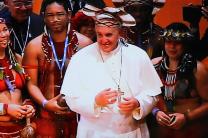 In one of the most inclusive gestures of his visit here, Pope Francis donned a headdress offered to him from an indigenous South American Indian at a ceremony in the city´s grand municipal theater.