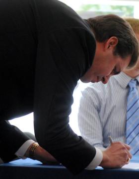 Gonzaga President Thayne McCulloh signs the St. Francis Pledge to Care.