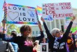 (RNS7-april27) Ikeita Cantu, left, and Carmen Guzman, of McLean, Va., hold signs in front of the Supreme Court on April 28, 2015 as justices inside considered arguments about legalizing same-sex marriage nationwide. They were married in 2009 in Canada. For use with RNS-SCOUTS-MARRIAGE, transmitted on April 27, 2015, Religion News Service photo by Adelle M. Banks
