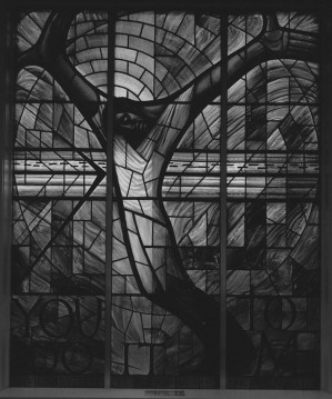 "Stained glass window donated by the people of Wales after the 1963 bombing of the church. The south-facing window was designed by Welsh artist John Petts and depicts a black Christ with his arms outstretched. The right hand symbolizes oppression, his left is asking for forgiveness. The words ""You do it to me"" refer to Christ's parable of the sheep and the goats. Photographer Jet Lowe"