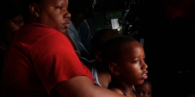 Survivors, pulled from their apartment building in New Orleans by Coast Guard rescue swimmer, sit on floor rescue helicopter.  Survivors, pulled from their apartment building in New Orleans by a Coast Guard rescue swimmer, sit on the floor of an HH-65 Jayhawk rescue helicopter August 30, 2005. Hellish scenes of death, damage, and chaos wracked the U.S. Gulf Coast on Wednesday as overwhelmed authorities tried to rescue the living and count the dead amid the destruction left by powerful Hurricane Katrina. New Orleans was filling with water after an initial attempt to stop a leaking levee failed, while police fought a losing battle to stop widespread looting in the stricken city. Photo taken on August 30, 2005. REUTERS/U.S. Coast Guard/Petty Officer 2nd Class NyxoLyno Cangemi/Handout - RTRM2GG