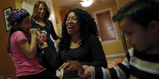 Mercedes Santos (2nd R) shares a laugh with her partner Theresa Volpe (2nd L) while playing cards with their son Jaidon (R) and daughter Ava at their home in Chicago, Illinois, December 22, 2012. Santos and Volpe are a same-sex couple raising two of their biological children as they struggle to get same-sex marriages passed into law in Illinois. Picture taken December 22, 2012.    REUTERS/Jim Young (UNITED STATES - Tags: SOCIETY) - RTXXX4H