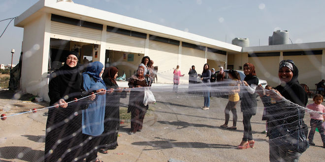 Syrian refugee women in northern Lebanon display part of a 100 metre fishing net that they've made, as part of a livelihoods training project supported by UK aid/Wikipedia photo by UK Department for International Development