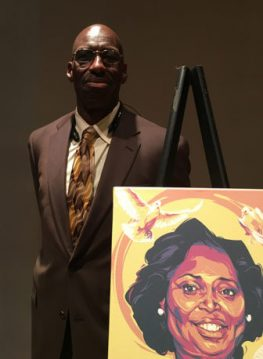 Melvin Graham, alongside a portrait of his sister, Cynthia Graham Hurd, a librarian killed in the massacre at Emanuel AME church on June 17, 2015. Graham and his brothers have established a foundation that honors their slain sister by providing books to disadvantaged young people. RNS photo by Lauren Markoe