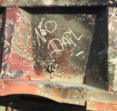 Graffiti drawn in the soot on a burnt military vehicle that is part of a barricade on the highway into the Two Spirits Camp. Photo by Elizabeth Schindler