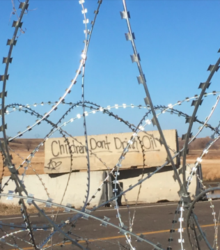 Graffiti on barricades that can be seen through razor wire photo by Elizabeth Schindler